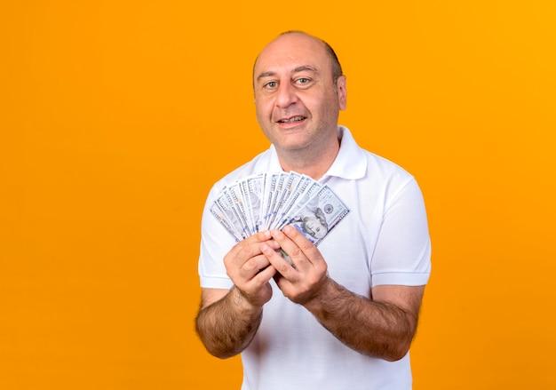 Lächelnder lässiger reifer mann, der bargeld lokalisiert auf gelber wand hält
