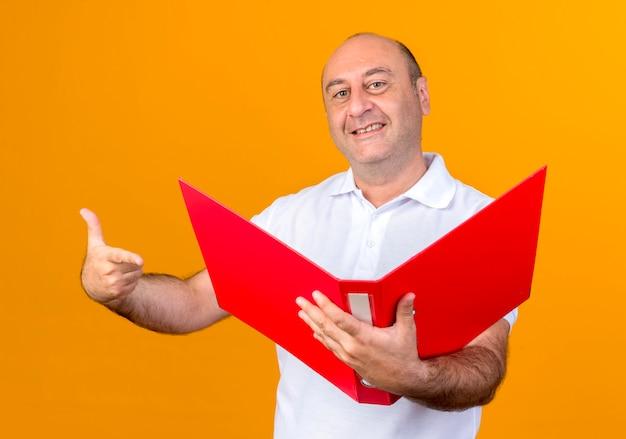 Lächelnder lässiger reifer mann, der hält und zeigt auf ordner lokalisiert auf gelb