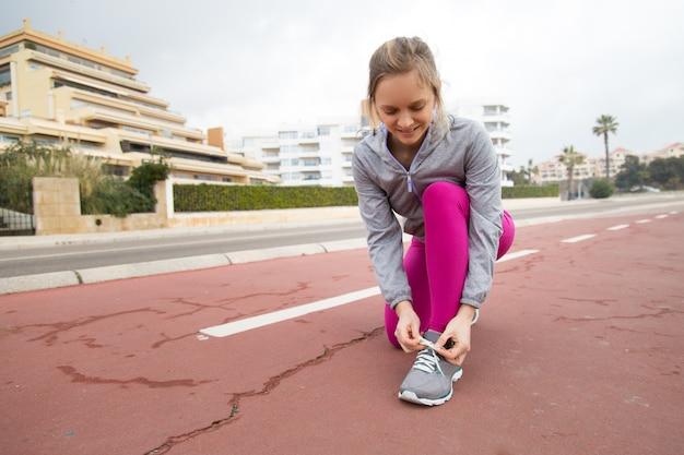 Lächelnder läufer, der spitze des sportschuhs auf stadion bindet