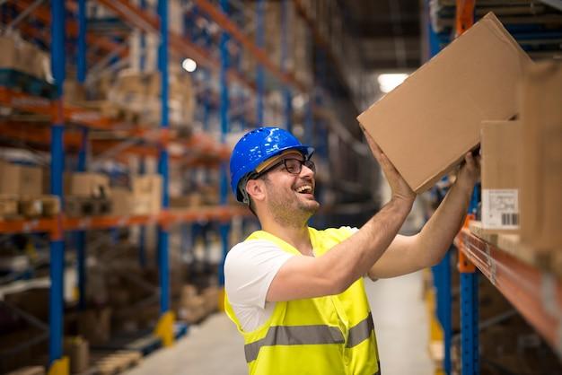 Lächelnder lagerarbeiter, der kisten auf dem regal bewegt