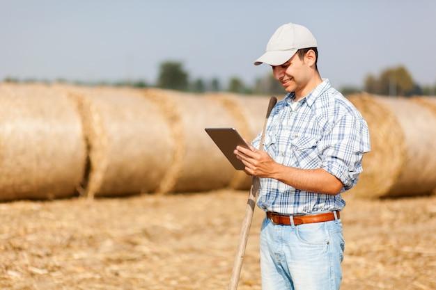 Lächelnder landwirt, der eine tablette verwendet