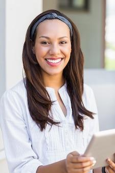 Lächelnder lehrer, der digitale tablette im klassenzimmer verwendet