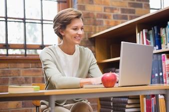 Lächelnder lehrer, der laptop an einem schreibtisch verwendet