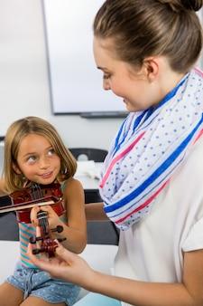 Lächelnder lehrer, der mädchen hilft, geige im klassenzimmer zu spielen