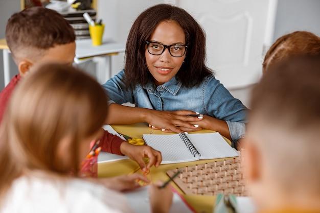 Lächelnder lehrer, der schulkinder während des unterrichts anschaut