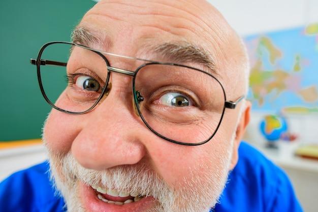 Lächelnder lehrer mit lustigem gesicht. lehrertag. lern-, bildungs- und schulkonzept.