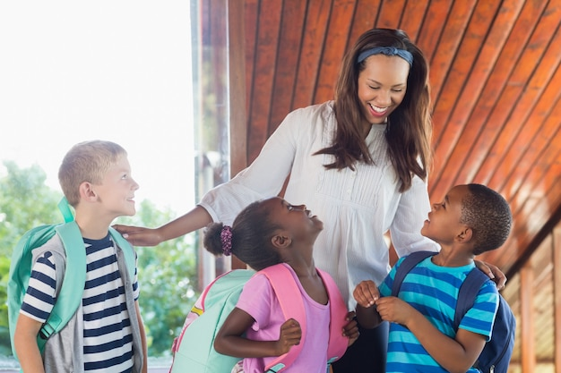 Lächelnder lehrer und kinder, die miteinander sprechen
