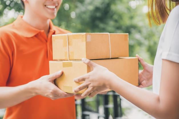 Lächelnder lieferbote, der paket an eine frau liefert