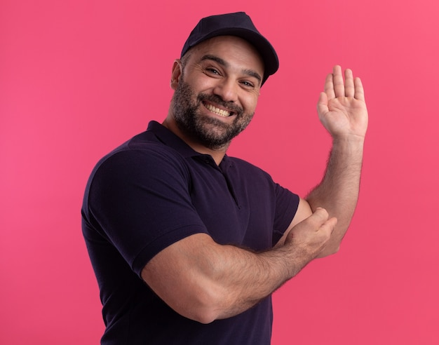 Lächelnder lieferbote mittleren alters in uniform und kappenspitzen mit den händen hinten isoliert auf rosa wand mit kopienraum