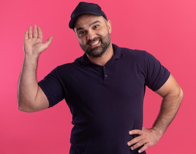 Lächelnder lieferbote mittleren alters in uniform und mütze, die hand auf hüfte halten und hallo-geste lokalisiert auf rosa wand zeigen