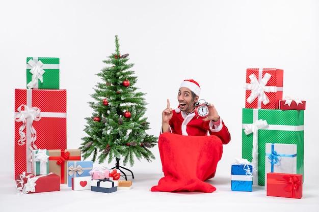 Lächelnder lustiger junger mann feiern neujahrs- oder weihnachtsfeiertag, der auf dem boden sitzt und uhr hält, die oben nahe geschenke und geschmückten weihnachtsbaum zeigt