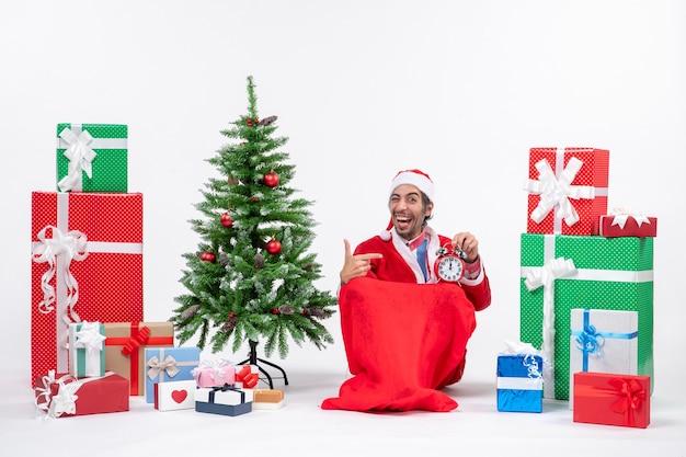 Lächelnder lustiger junger mann feiern neujahrs- oder weihnachtsfeiertag, der auf dem boden sitzt und uhr nahe geschenken und geschmücktem weihnachtsbaum hält