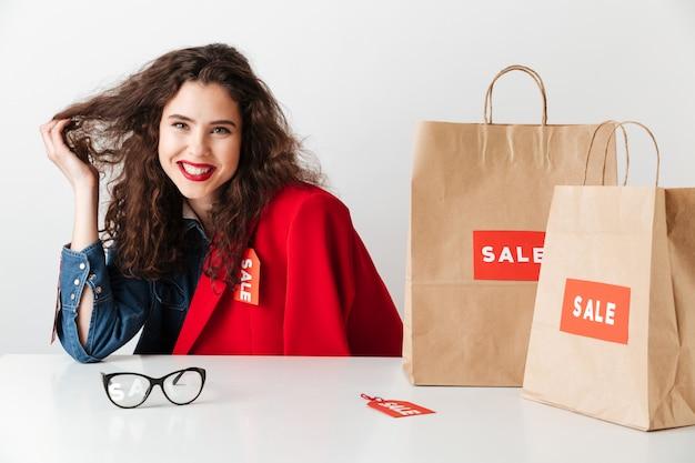 Lächelnder mädchen-shopaholic, der mit papiereinkaufstüten sitzt