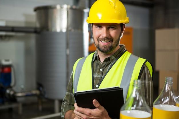 Lächelnder männlicher arbeiter, der digitales tablett in fabrik hält