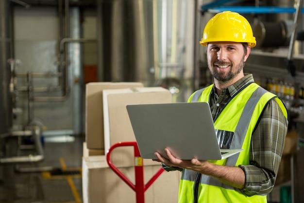 Lächelnder männlicher arbeiter, der laptop im verteilungslager benutzt