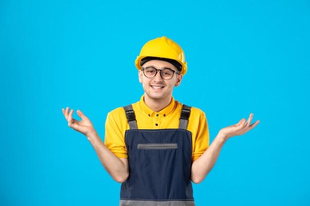 Lächelnder männlicher arbeiter der vorderansicht in der uniform und im helm auf blau