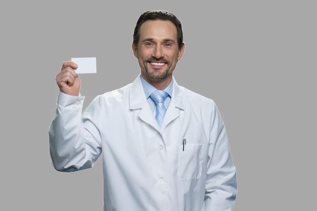 Lächelnder männlicher arzt, der visitenkarte hält. erfolgreicher wissenschaftler oder forscher, der visitenkarte mit leerem kopienraum zeigt.