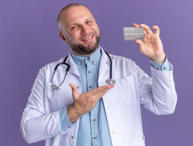 Lächelnder männlicher arzt mittleren alters, der ein medizinisches gewand und ein stethoskop trägt und auf die kreditkarte isoliert auf lila wand zeigt