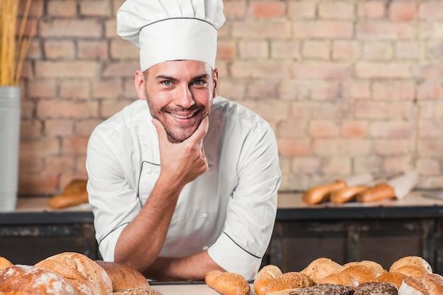 Lächelnder männlicher bäcker an der bäckerei