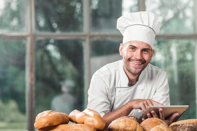 Lächelnder männlicher bäcker, der auf tabelle mit gebackenen broten gegen fenster sich lehnt