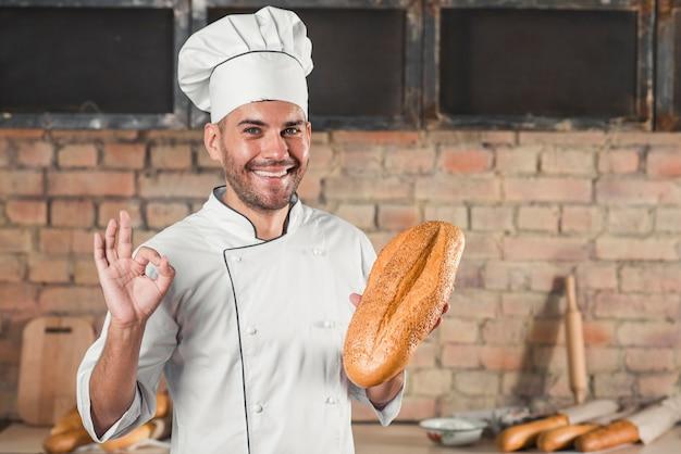 Lächelnder männlicher bäcker, der das laib zeigt okayhandzeichen hält, gestikulieren