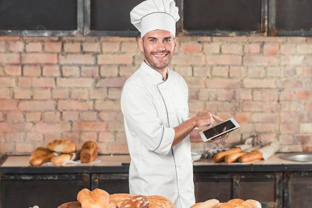 Lächelnder männlicher bäcker, der die digitale tabelle steht hinter der tabelle mit gebackenen broten verwendet