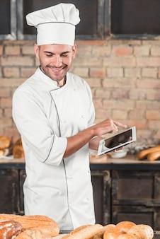 Lächelnder männlicher bäcker, der die digitale tablette betrachtet gebackenes brot auf tabelle verwendet