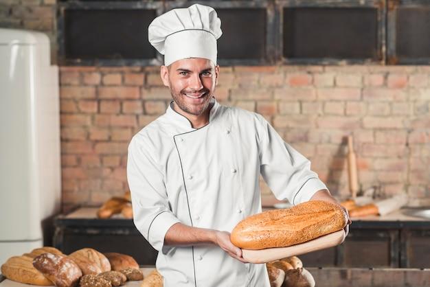 Lächelnder männlicher bäcker, der gebackenes brot auf hackendem brett hält