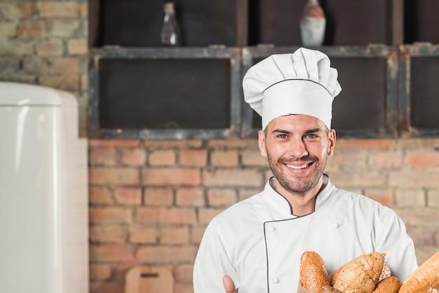 Lächelnder männlicher bäcker, der stangenbrote hält