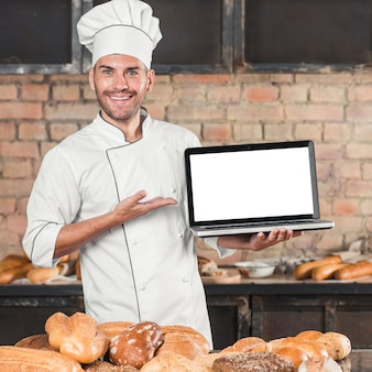 Lächelnder männlicher bäcker, der vor tabelle mit unterschiedlicher art von broten steht