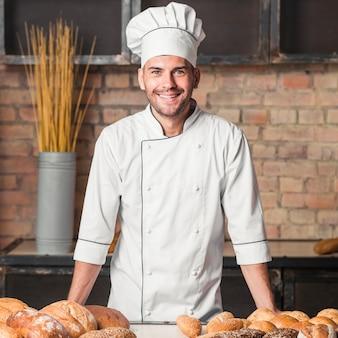Lächelnder männlicher bäcker mit frisch gebackenen broten