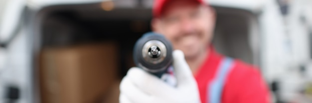 Lächelnder männlicher baumeister mit bohrmaschine nahaufnahme