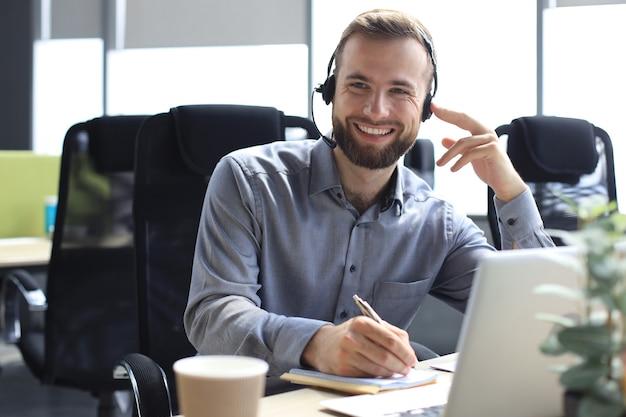 Lächelnder männlicher call-center-betreiber mit kopfhörern, der in einem modernen büro sitzt, online-informationen in einem laptop konsultiert, informationen in einer datei nachschlägt, um dem kunden zu helfen. Premium Fotos