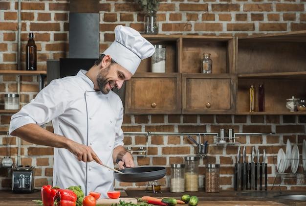 Lächelnder männlicher chef, der lebensmittel in der küche zubereitet