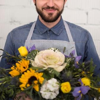 Lächelnder männlicher florist mit schönem blumenblumenstrauß