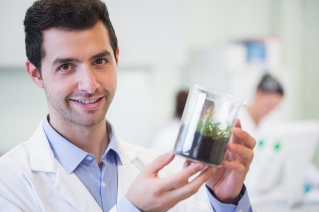 Lächelnder männlicher forscher, der jungpflanze am labor hält