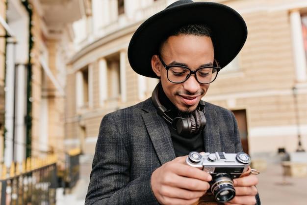 Lächelnder männlicher fotograf in den kopfhörern, die auf stadtstraße stehen. foto im freien des fröhlichen afrikanischen jungen mannes in der karierten jacke, die kamera betrachtet.