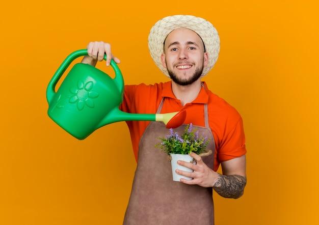 Lächelnder männlicher gärtner, der gartenhut trägt, hält bewässerungsdose, die vorgibt, blumen im blumentopf zu gießen