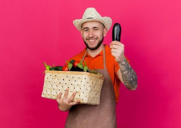 Lächelnder männlicher gärtner, der gartenhut trägt, hält gemüsekorb und aubergine