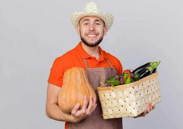 Lächelnder männlicher gärtner, der gartenhut trägt, hält kürbis und gemüsekorb suchen