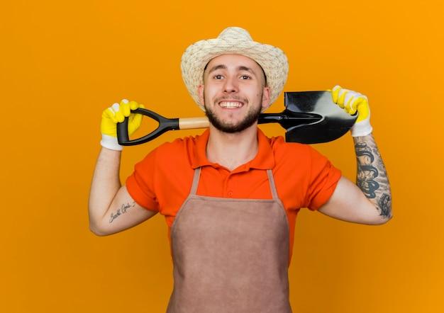 Lächelnder männlicher gärtner, der gartenhut und handschuhe trägt, hält spaten hinter dem hals, der schaut