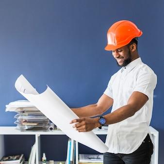 Lächelnder männlicher ingenieur, der plan auf arbeitsplatz betrachtet