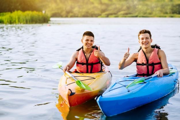 Lächelnder männlicher kayaker zwei, der daumen herauf zeichen zeigt