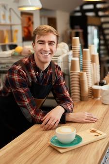 Lächelnder männlicher kellner in schürze mit tasse heißem getränk im café, barista freut sich, in der cafeteria zu arbeiten
