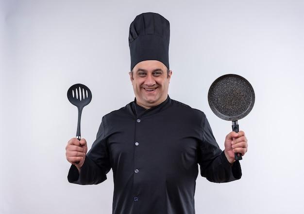 Lächelnder männlicher koch mittleren alters in der kochuniform, die spatel und pfanne hält