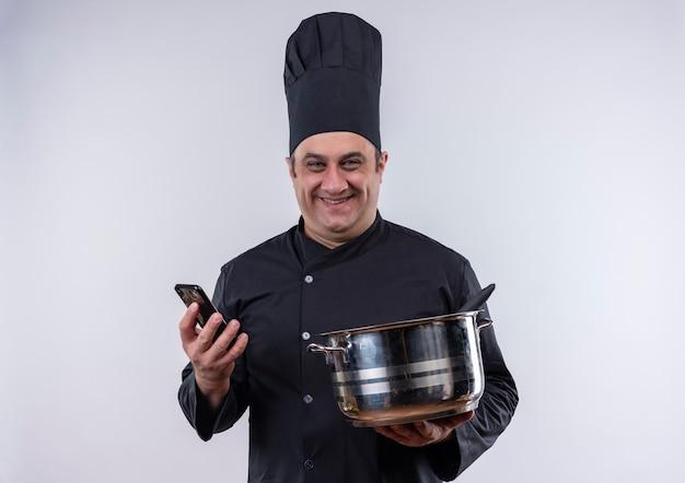 Lächelnder männlicher koch mittleren alters in der kochuniform, die topf und telefon hält