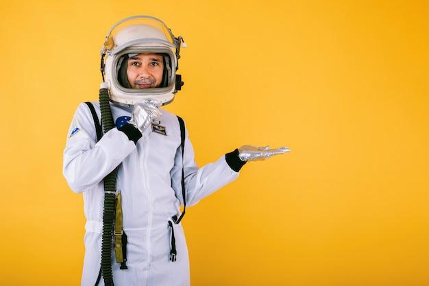 Lächelnder männlicher kosmonaut in raumanzug und helm, mit der hand nach rechts zeigend, auf gelber wand.