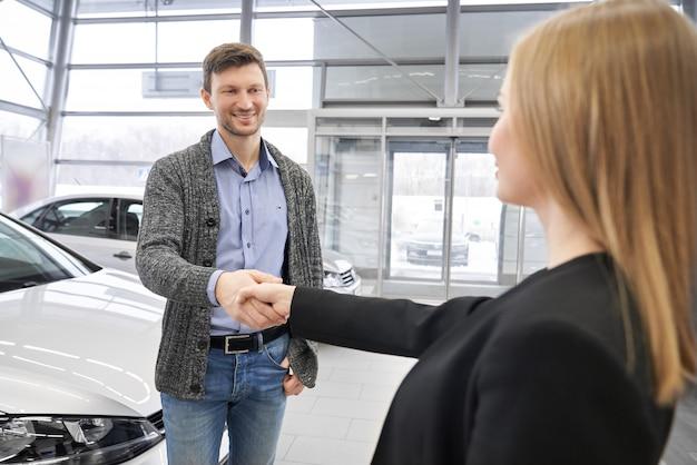 Lächelnder männlicher kunde, der dem verkäufer im autohaus händeschütteln schüttelt