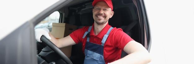 Lächelnder männlicher kurierfahrer, der auto nahaufnahme fährt