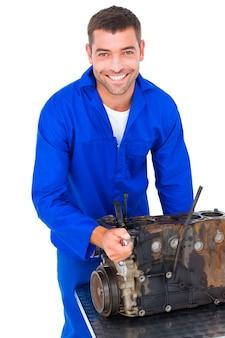 Lächelnder männlicher machanic, der automotor repariert